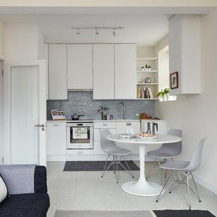 ダブリンの小さい北欧スタイルのおしゃれなキッチン (アンダーカウンターシンク、フラットパネル扉のキャビネット、白いキャビネット、珪岩カウンター、緑のキッチンパネル、ガラスタイルのキッチンパネル、シルバーの調理設備の、クッションフロア、アイランドなし、白い床、白いキッチンカウンター) の写真