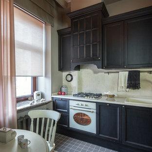 Идея дизайна: угловая кухня в классическом стиле с обеденным столом, черными фасадами, белым фартуком, белой техникой, серым полом, накладной раковиной и фасадами с утопленной филенкой без острова