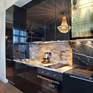 Small contemporary kitchen designs - Example of a small trendy kitchen design in Moscow with a drop-in sink, flat-panel cabinets, black cabinets, black appliances, marble countertops, black backsplash and stone slab backsplash