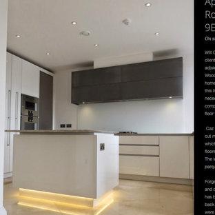 ロンドンの巨大なコンテンポラリースタイルのおしゃれなキッチン (一体型シンク、フラットパネル扉のキャビネット、ターコイズのキャビネット、大理石カウンター、大理石のキッチンパネル) の写真