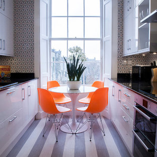Photo of a small contemporary galley kitchen/diner in Other with a built-in sink, flat-panel cabinets, white cabinets, granite worktops, black splashback, stainless steel appliances and lino flooring.