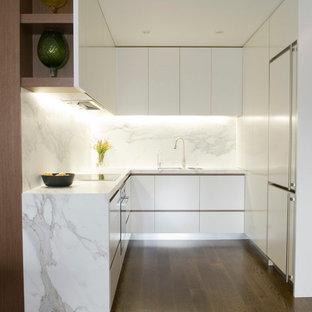 На фото: маленькая п-образная кухня в стиле модернизм с белыми фасадами, мраморной столешницей, техникой под мебельный фасад, белым фартуком и темным паркетным полом без острова с