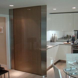 Diseño de cocina en L, abierta, con armarios con paneles lisos, puertas de armario blancas, salpicadero metalizado, salpicadero con efecto espejo, electrodomésticos de acero inoxidable y suelo de madera clara