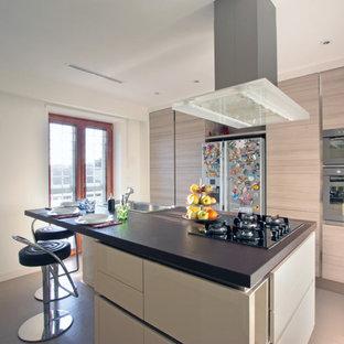 Immagine di una grande cucina moderna con ante beige, elettrodomestici in acciaio inossidabile, pavimento con piastrelle in ceramica, isola, lavello da incasso e ante lisce