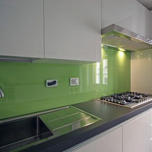 Small contemporary eat-in kitchen pictures - Eat-in kitchen - small contemporary galley medium tone wood floor eat-in kitchen idea in Rome with a drop-in sink, flat-panel cabinets, white cabinets, quartz countertops, green backsplash, glass sheet backsplash, stainless steel appliances and an island