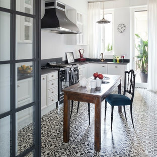 Medium sized country l-shaped kitchen/diner in Milan with recessed-panel cabinets, white cabinets, white splashback, black appliances, ceramic flooring, no island and multi-coloured floors.