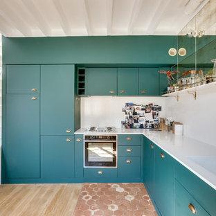 Idée de décoration pour une grand cuisine ouverte design en L avec des portes de placards vertess, aucun îlot, un évier intégré, un placard à porte plane, une crédence blanche, un électroménager noir, un sol en bois clair, un plan de travail blanc et un sol marron.