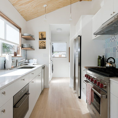 Enclosed kitchen - mid-sized scandinavian galley light wood floor enclosed kitchen idea in Los Angeles with a single-bowl sink, flat-panel cabinets, white cabinets, quartz countertops, blue backsplash, porcelain backsplash and stainless steel appliances