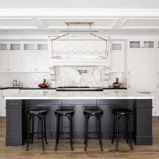 Inspiration for a traditional u-shaped eat-in kitchen in Perth with a farmhouse sink, recessed-panel cabinets, white cabinets, white splashback, medium hardwood floors, with island, brown floor and white benchtop.