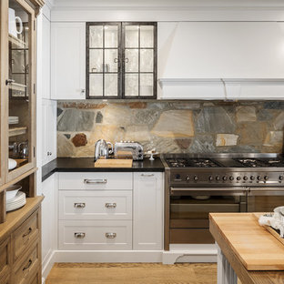This is an example of a large country kitchen in Perth with shaker cabinets, granite benchtops, brown splashback, stainless steel appliances, medium hardwood floors, with island, black benchtop, white cabinets and slate splashback.