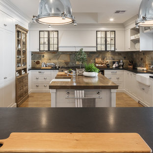 This is an example of a large country kitchen in Perth with shaker cabinets, grey cabinets, granite benchtops, brown splashback, stainless steel appliances, medium hardwood floors, a farmhouse sink, black benchtop, slate splashback and multiple islands.