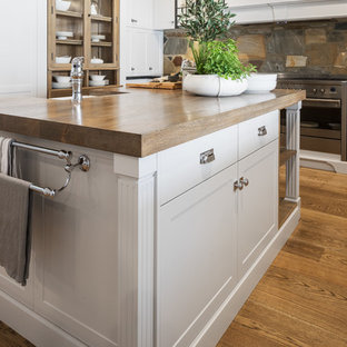 Large country kitchen in Perth with shaker cabinets, grey cabinets, brown splashback, stainless steel appliances, medium hardwood floors, with island, wood benchtops, a farmhouse sink, slate splashback and brown benchtop.