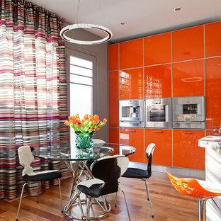Modern inredning av ett kök och matrum, med släta luckor, orange skåp, mellanmörkt trägolv och en köksö