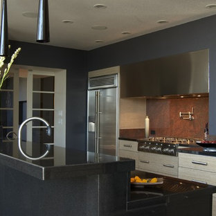 Idee per una cucina parallela design con ante lisce, ante in legno chiaro, paraspruzzi rosso, paraspruzzi in lastra di pietra e elettrodomestici in acciaio inossidabile