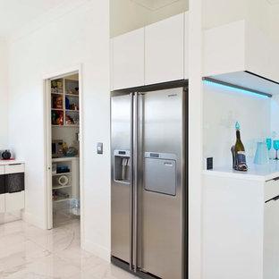 クライストチャーチの広いモダンスタイルのおしゃれなキッチン (アンダーカウンターシンク、フラットパネル扉のキャビネット、白いキャビネット、人工大理石カウンター、黄色いキッチンパネル、ガラス板のキッチンパネル、シルバーの調理設備、セラミックタイルの床、白い床) の写真