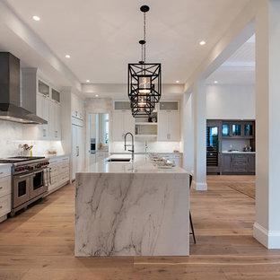 Offene Moderne Küche in L-Form mit Unterbauwaschbecken, Schrankfronten mit vertiefter Füllung, weißen Schränken, Küchengeräten aus Edelstahl, braunem Holzboden, zwei Kücheninseln, braunem Boden und weißer Arbeitsplatte in Miami