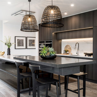 Design ideas for a contemporary galley kitchen in Gold Coast - Tweed with an undermount sink, flat-panel cabinets, black cabinets, white splashback, medium hardwood floors, with island, brown floor and white benchtop.
