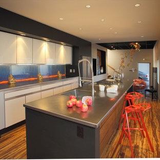 Zweizeilige, Geschlossene Moderne Küche mit Küchengeräten aus Edelstahl, integriertem Waschbecken, flächenbündigen Schrankfronten, beigen Schränken, Edelstahl-Arbeitsplatte und Glasrückwand in Sonstige