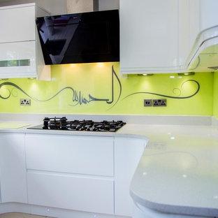 Diseño de cocina actual con salpicadero amarillo y salpicadero de vidrio templado