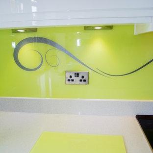 Imagen de cocina contemporánea con salpicadero amarillo y salpicadero de vidrio templado