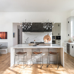 Photo of a contemporary u-shaped kitchen/diner in Austin with shaker cabinets, grey cabinets, white splashback, stainless steel appliances, light hardwood flooring, an island and brown floors.