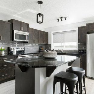 カルガリーの中サイズのインダストリアルスタイルのおしゃれなキッチン (アンダーカウンターシンク、シェーカースタイル扉のキャビネット、中間色木目調キャビネット、御影石カウンター、黒いキッチンパネル、セラミックタイルのキッチンパネル、シルバーの調理設備の、淡色無垢フローリング) の写真