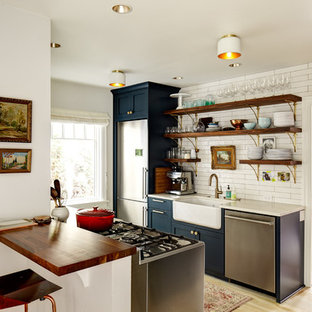 Photo of a country galley separate kitchen in Seattle with a farmhouse sink, open cabinets, blue cabinets, white splashback, stainless steel appliances, light hardwood floors and no island.