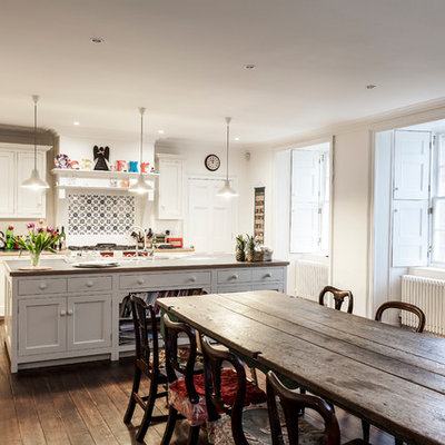 Eat-in kitchen - traditional galley medium tone wood floor eat-in kitchen idea in Edinburgh with an island, shaker cabinets, white cabinets, multicolored backsplash, mosaic tile backsplash and stainless steel appliances