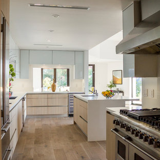 Inspiration for a large midcentury l-shaped open plan kitchen in Los Angeles with an integrated sink, flat-panel cabinets, light wood cabinets, laminate benchtops, stainless steel appliances, medium hardwood floors and with island.