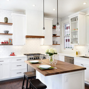 Large transitional kitchen inspiration - Example of a large transitional l-shaped dark wood floor and brown floor kitchen design in Orange County with an undermount sink, recessed-panel cabinets, white cabinets, white backsplash, subway tile backsplash, stainless steel appliances, an island and wood countertops
