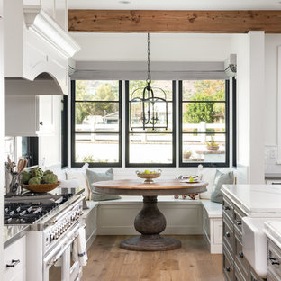 Farmhouse eat-in kitchen pictures - Cottage galley medium tone wood floor and brown floor eat-in kitchen photo in Phoenix with a farmhouse sink, gray cabinets and white countertops