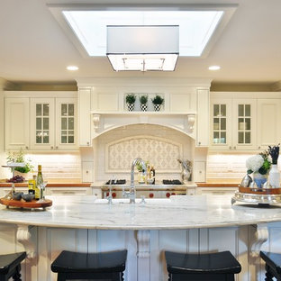 Inspiration for a l-shaped eat-in kitchen in Phoenix with raised-panel cabinets, white cabinets, marble benchtops, white splashback, subway tile splashback and stainless steel appliances.
