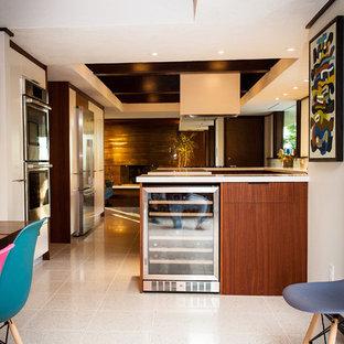 Modelo de cocina retro, grande, con armarios con paneles lisos, puertas de armario de madera oscura, encimera de cuarcita, electrodomésticos de acero inoxidable, suelo de terrazo y una isla