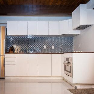 Modelo de cocina en L, vintage, pequeña, abierta, con armarios con paneles lisos, puertas de armario blancas, encimera de madera, salpicadero azul, salpicadero de azulejos de vidrio, electrodomésticos de acero inoxidable y suelo de terrazo