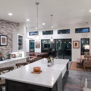 フェニックスの広いトランジショナルスタイルのおしゃれなキッチン (エプロンフロントシンク、白いキャビネット、珪岩カウンター、レンガのキッチンパネル、シルバーの調理設備、コンクリートの床、グレーの床、白いキッチンカウンター、レイズドパネル扉のキャビネット、マルチカラーのキッチンパネル) の写真