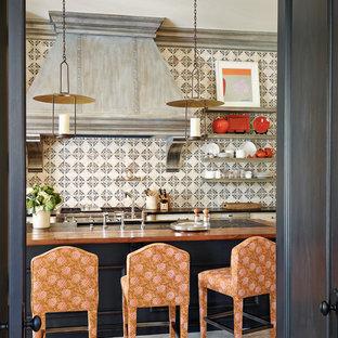 フェニックスの中サイズの地中海スタイルのおしゃれなキッチン (黒いキャビネット、マルチカラーのキッチンパネル、木材カウンター、アンダーカウンターシンク、セラミックタイルのキッチンパネル、シルバーの調理設備の) の写真