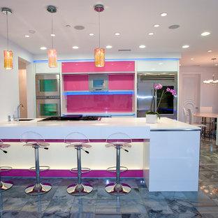 Diseño de cocina comedor contemporánea, grande, con electrodomésticos de acero inoxidable, fregadero bajoencimera, armarios tipo vitrina, encimera de acrílico, salpicadero rosa, salpicadero de vidrio templado, suelo de baldosas de porcelana y una isla
