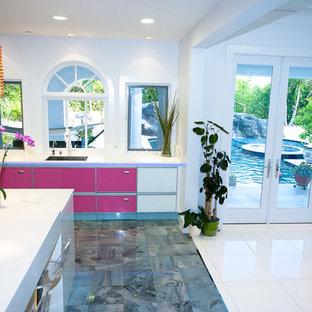 Große Moderne Wohnküche mit Unterbauwaschbecken, Glasfronten, Mineralwerkstoff-Arbeitsplatte, Küchenrückwand in Rosa, Glasrückwand, Küchengeräten aus Edelstahl, Porzellan-Bodenfliesen und Kücheninsel in Los Angeles