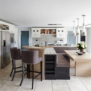 Contemporary open plan kitchen in London with stainless steel appliances, an island, flat-panel cabinets and granite worktops.