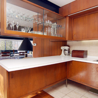 1960s open concept kitchen photo in Other with a drop-in sink, flat-panel cabinets, medium tone wood cabinets, laminate countertops and beige backsplash
