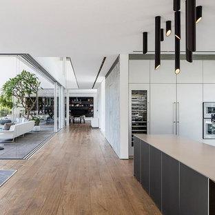 Modern inredning av ett mycket stort linjärt kök med öppen planlösning, med en integrerad diskho, släta luckor, vita skåp, bänkskiva i kvarts, ljust trägolv och flera köksöar
