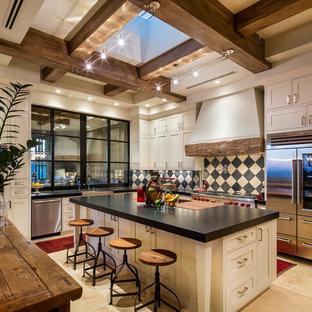 フェニックスのサンタフェスタイルのおしゃれなキッチン (シェーカースタイル扉のキャビネット、ベージュのキャビネット、マルチカラーのキッチンパネル、シルバーの調理設備、ベージュの床、黒いキッチンカウンター) の写真