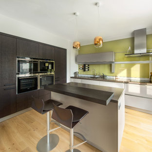 Inspiration for a small contemporary l-shaped kitchen/diner in Oxfordshire with an integrated sink, flat-panel cabinets, grey cabinets, composite countertops, green splashback, glass sheet splashback, black appliances, light hardwood flooring, an island and grey worktops.