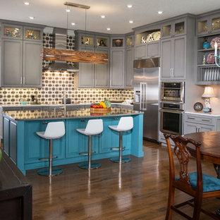 Eklektische Wohnküche in L-Form mit Schrankfronten mit vertiefter Füllung, türkisfarbenen Schränken, bunter Rückwand, Küchengeräten aus Edelstahl, braunem Holzboden, Kücheninsel, braunem Boden und grauer Arbeitsplatte in Sonstige