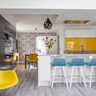 Ejemplo de cocina comedor en U, actual, con armarios con paneles lisos, puertas de armario blancas, salpicadero naranja, salpicadero de vidrio templado, península y suelo gris