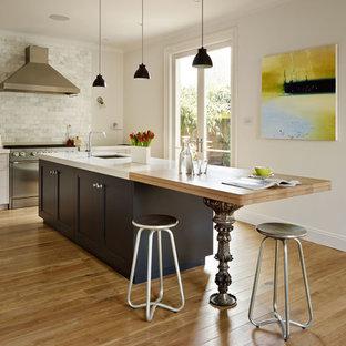 ロンドンの中サイズのエクレクティックスタイルのおしゃれなキッチン (落し込みパネル扉のキャビネット、白いキッチンパネル、大理石のキッチンパネル、シルバーの調理設備、淡色無垢フローリング、黒いキャビネット、木材カウンター、茶色い床) の写真
