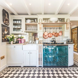 This is an example of a farmhouse single-wall kitchen in Berkshire with a belfast sink, shaker cabinets, white cabinets, grey splashback, ceramic splashback, coloured appliances, ceramic flooring and no island.