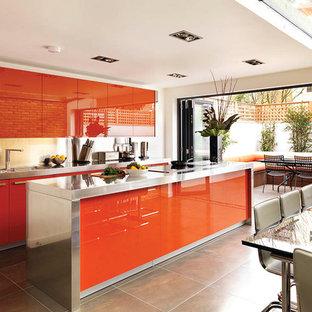 Cette photo montre une cuisine américaine tendance avec un évier intégré, un placard à porte plane, un plan de travail en inox, un sol en carrelage de porcelaine, un îlot central et des portes de placard oranges.