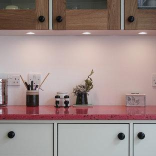 Moderne Küche mit Arbeitsplatte aus Recyclingglas, bunten Elektrogeräten, Kücheninsel und rosa Arbeitsplatte in London
