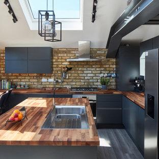 ロンドンの広いコンテンポラリースタイルのおしゃれなキッチン (ドロップインシンク、フラットパネル扉のキャビネット、木材カウンター、シルバーの調理設備、淡色無垢フローリング、茶色い床、茶色いキッチンカウンター、黒いキャビネット、茶色いキッチンパネル、レンガのキッチンパネル) の写真